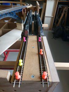 Zum Fixieren werden Pinnwandnadeln gebraucht, auf der Brücke sind es Gewichte, die das Gleis in der richtigen Lage halten